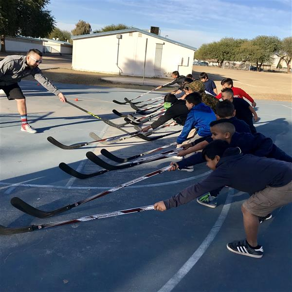 A Phoenix Coyote hockey coach with a group of students. They all have hockey sticks in their hands.