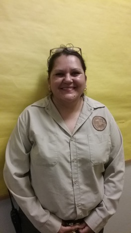 Custodian in brown custodial uniform smiling. She is in from of a yellow backdrop.
