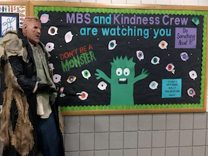 Man dressed as monster in front of board which reads MBS and kindness crew are watching you.