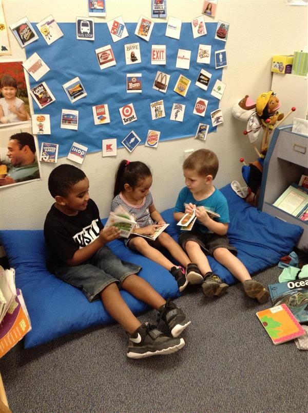 Three children in library reading