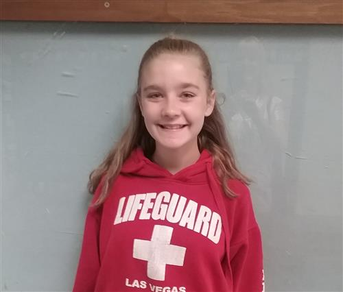 Girl in a red sweatshirt smiling for a picture.