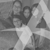 "Four girls standing by a tree with transparent ""A"" logo overlayed."